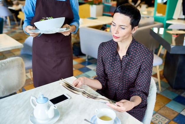 Femme élégante en attente de commande au café