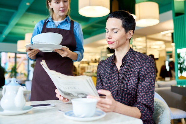 Femme élégante en attente de nourriture au café