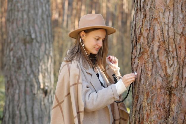 Femme élégante au chapeau écoute un arbre avec un stéthoscope dans la forêt, concept aime l'environnement