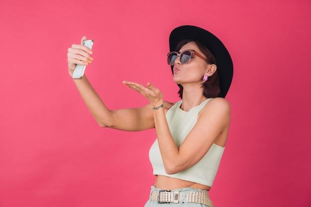 Femme élégante au chapeau et lunettes de soleil sur le mur rouge rose