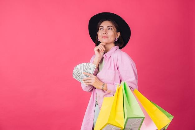 Femme élégante au chapeau sur un mur rouge rose