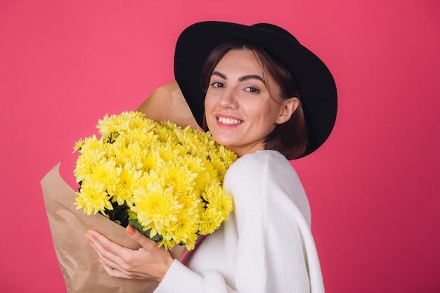 Femme élégante au chapeau sur mur rouge
