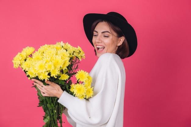 Femme élégante au chapeau et pull blanc décontracté sur un mur rouge rose