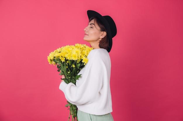 Femme élégante au chapeau et pull blanc décontracté sur mur rouge