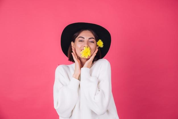 Femme élégante au chapeau, souriant avec deux asters jaunes, mignon tenir une fleur dans l'humeur du printemps de la bouche, espace isolé des émotions heureuses