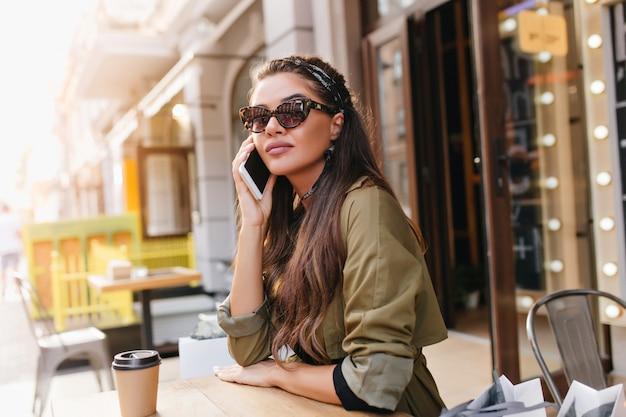 Femme élégante aux longs cheveux noirs appelant quelqu'un tout en se reposant dans un café en plein air avec une tasse de café