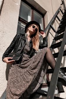 Femme élégante belle jeune mannequin en vêtements de mode avec une veste en cuir et une jupe vintage avec un sac à main noir posant dans les escaliers de la ville