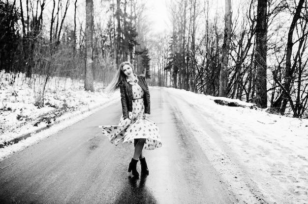 Femme élégante en blouson de cuir au jour d'hiver sur la route.