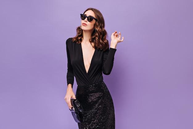 Femme élégante bouclée en jupe brillante et haut noir pose sur un mur violet