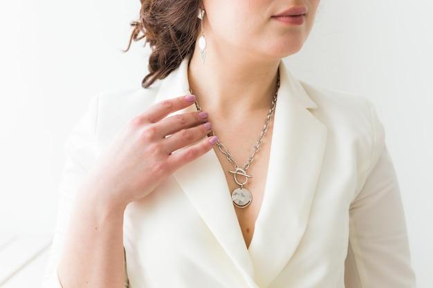 Femme élégante avec des boucles d'oreilles et chaîne de bijoux en argent