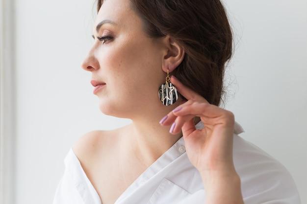 Femme élégante avec boucles d'oreilles, gros plan portrait.