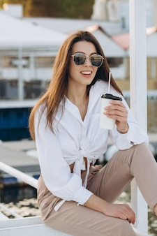 Une femme élégante, buvant un café et marchant le long du front de mer dans une chaude journée d'été au coucher du soleil