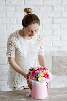 Femme élégante avec cadeau. bouquet de fleurs de luxe. boxe de roses colorées dans une boîte rose en forme de cylindre. beau et sensuel cadeau pour le 8 mars, saint valentin