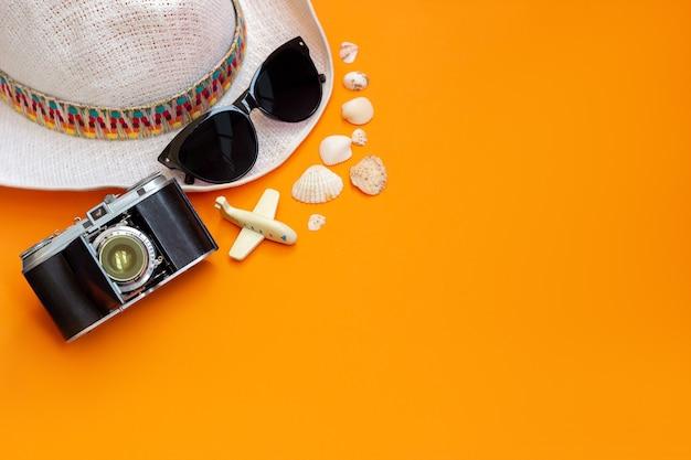 Femme élégante chapeau blanc de paille lunettes de soleil noires vieil appareil photo rétro, avion jouet et coquillages isolés sur un mur orange de couleur vive