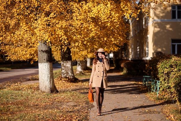 Une femme élégante en chapeau à larges bords et manteau beige marche dans la rue en automne.