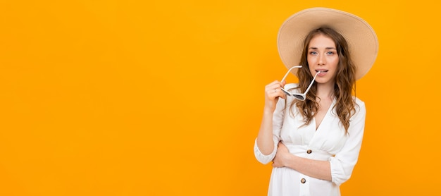 Femme élégante en chapeau et lunettes de soleil posant sur un jaune