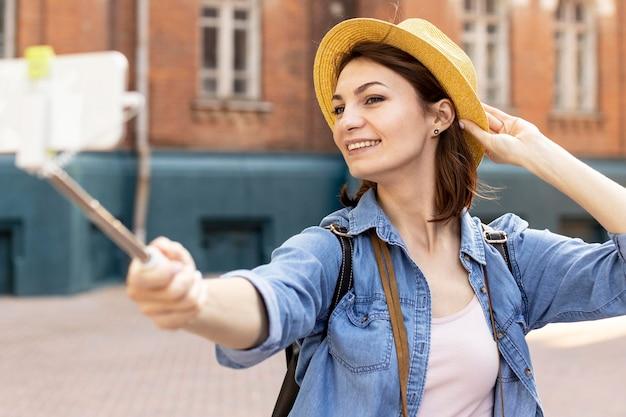 Femme élégante avec un chapeau prenant un selfie à l'extérieur