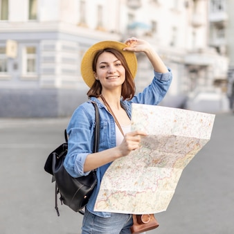 Femme élégante avec chapeau tenant la carte locale