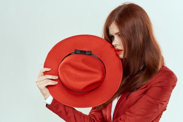 Femme élégante en chapeau de veste rouge tenant la lumière recadrée de cheveux longs