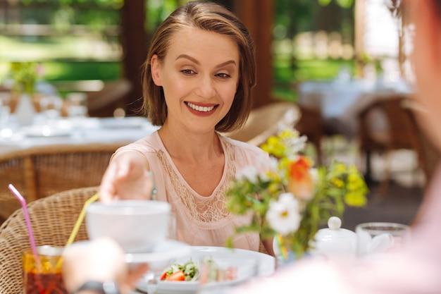 Femme élégante. charmante femme élégante se sentant incroyablement incroyable en assistant à la cérémonie du thé avec son mari