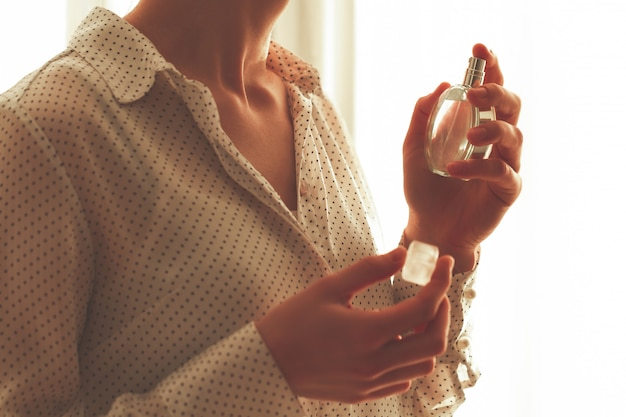 Femme élégante en chemisier avec une bouteille de parfum préféré.