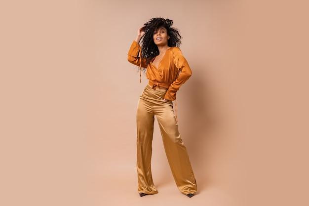 Femme élégante en chemisier orange et pantalon en soie dorée posant sur un mur beige. talons hauts. incroyables poils ondulés. longueur totale.
