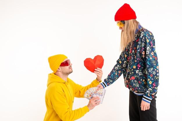 Femme élégante en choisissant de l'argent au lieu du cœur de l'homme sur fond blanc