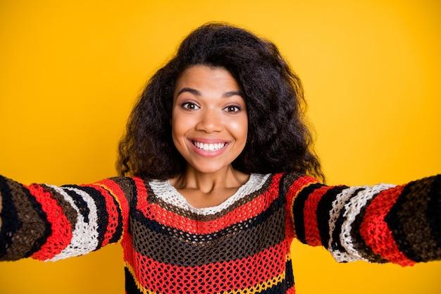 Femme élégante avec une coiffure afro posant contre le mur orange