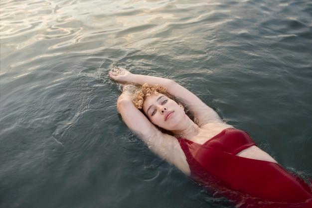 Femme élégante de coup moyen nageant