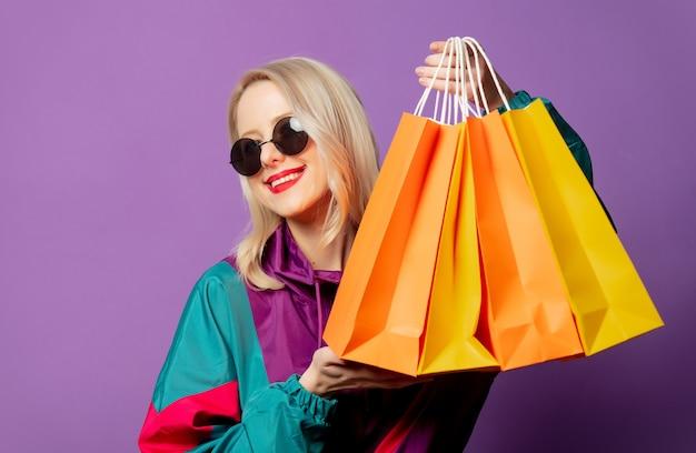 Femme élégante en coupe-vent des années 80 et lunettes de soleil rondes détient des sacs à provisions sur mur violet