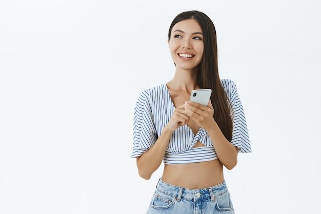 Femme élégante créative en haut court à la mode regardant à gauche avec un délicieux sourire tenant un smartphone