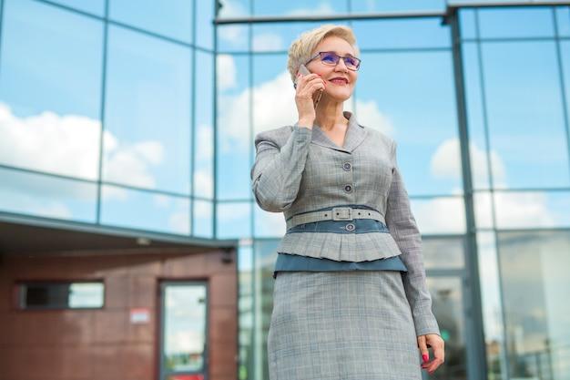 Femme élégante dans un costume et des lunettes, parler au téléphone