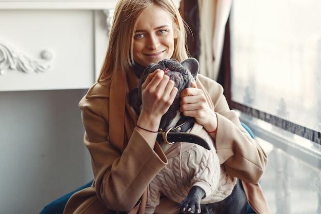 Femme élégante dans un manteau marron avec bouledogue noir
