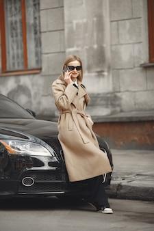Femme élégante dans un manteau marron dans une ville de printemps