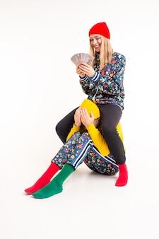 Femme élégante dans des vêtements colorés, choisir de l'argent au lieu de l'amour