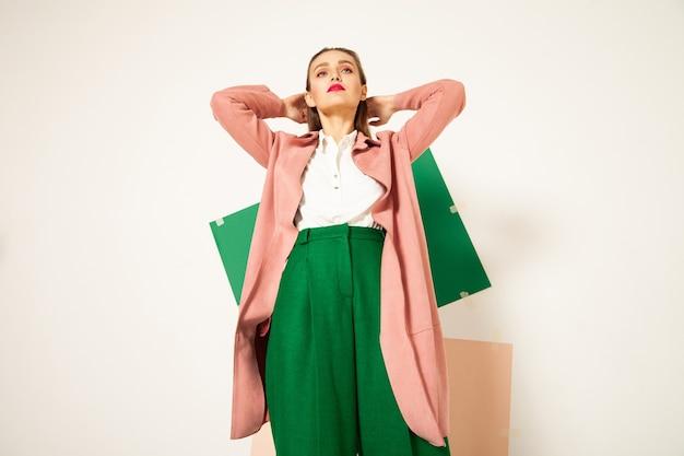 Femme élégante dans des vêtements colorés élégants en studio avec fond blanc