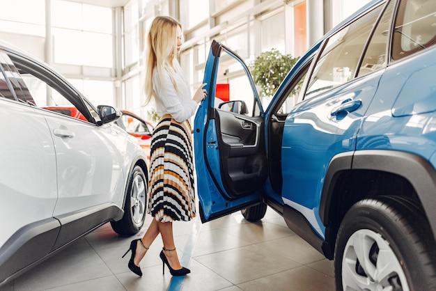 Femme élégante et élégante dans un salon de l'automobile