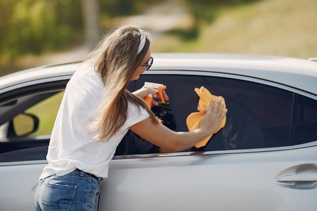 Femme élégante essuie la voiture avec un chiffon