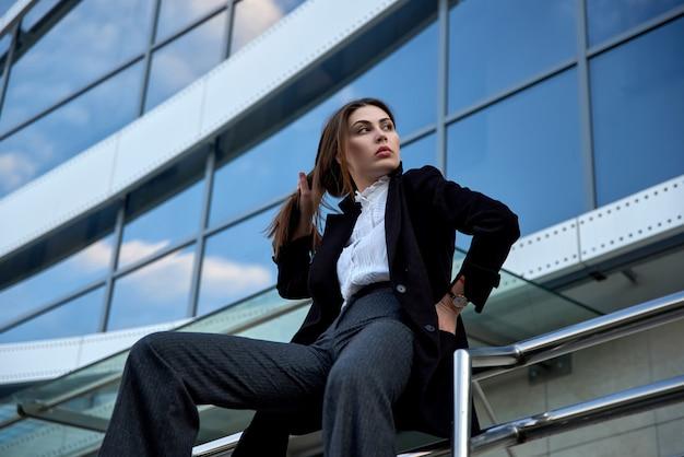 Femme élégante est assise sur la balustrade dans la rue