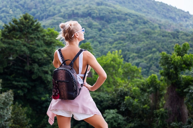 Femme élégante européenne touristique blogueur se dresse au sommet de la montagne avec une vue tropicale incroyable de l'île de koh samui thaïlande mode portrait en plein air de femme