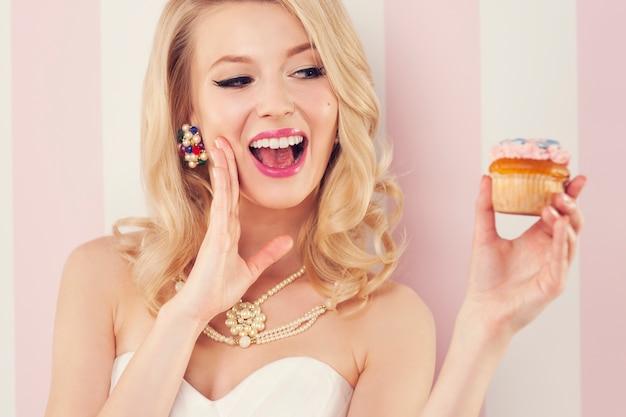 Femme élégante excitée avec muffin