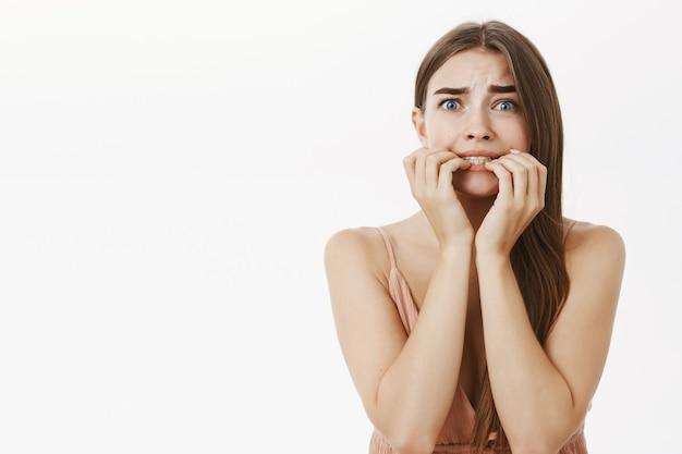 Femme élégante féminine timide et peu sûre de peur avec les cheveux bruns mordant les doigts regardant peur et panique effrayée exagérée faisant expression terrifiée sur mur gris