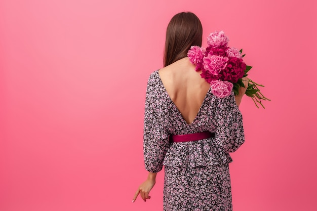 Femme élégante sur fond rose en robe à la mode d'été posant avec bouquet de fleurs de pivoine, vue de dos, tenue sexy