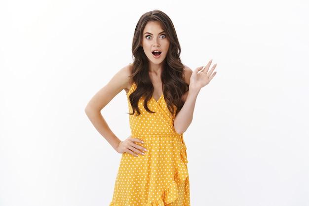 Une femme élégante et glamour choquée discute de rumeurs juteuses avec sa petite amie, réagissez émerveillée et surprise levant la main haletant secoua étonné, regarda la caméra excitée embusquée des nouvelles étonnantes cool, mur blanc