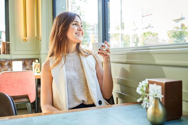Femme élégante et heureuse buvant un café dans un bar