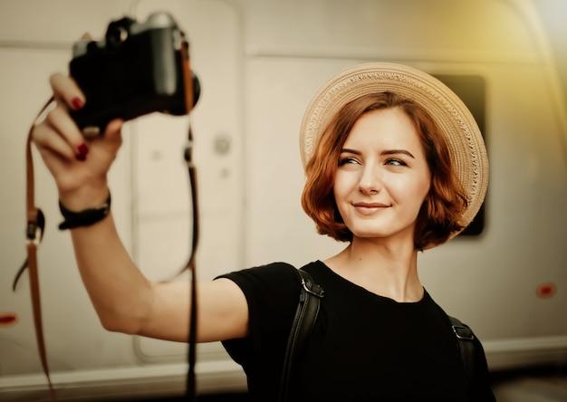Femme élégante hipster au chapeau fait un portrait de selfie à l'aide d'un appareil photo rétro