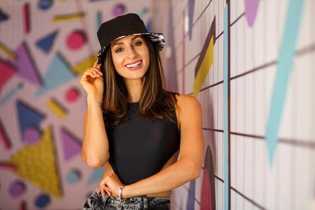 Femme élégante hipster élégante posant près d'un mur lumineux avec motif géométrique