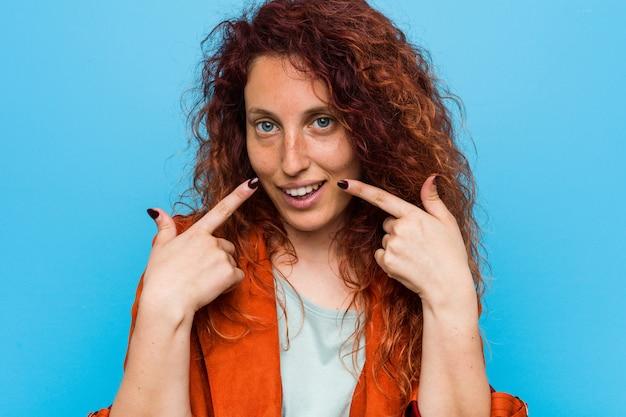 Femme élégante jeune rousse sourit, pointant les doigts vers la bouche.
