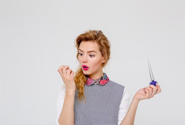 Femme élégante avec de longs cheveux, faire des manucures et souffler sur les ongles