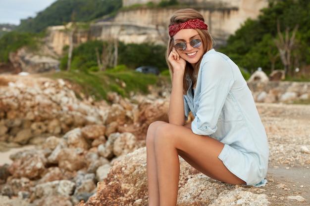 Femme élégante avec des lunettes de soleil assis sur la plage